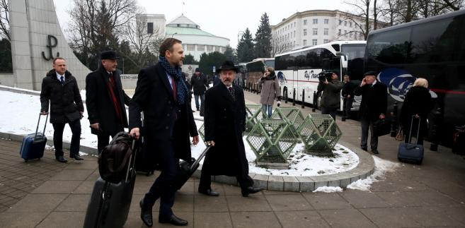 Posłowie PiS wsiadają do autokarów przed Sejmem