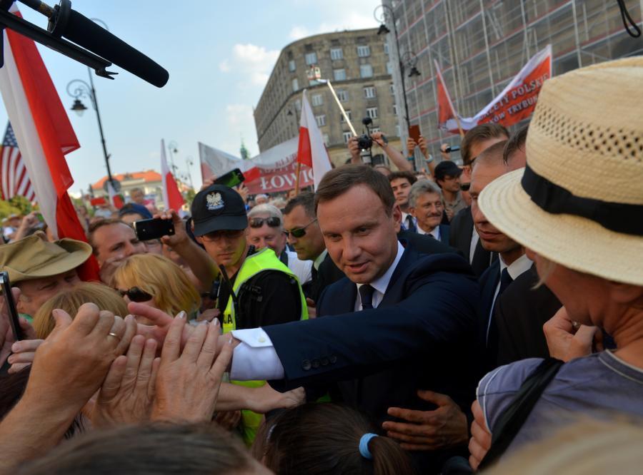 Prezydent Andrzej Duda rozmawia i wita się z osobami tłumnie zgromadzonymi na trasie jego przejścia z pl. Piłsudskiego do Pałacu Prezydenckiego.